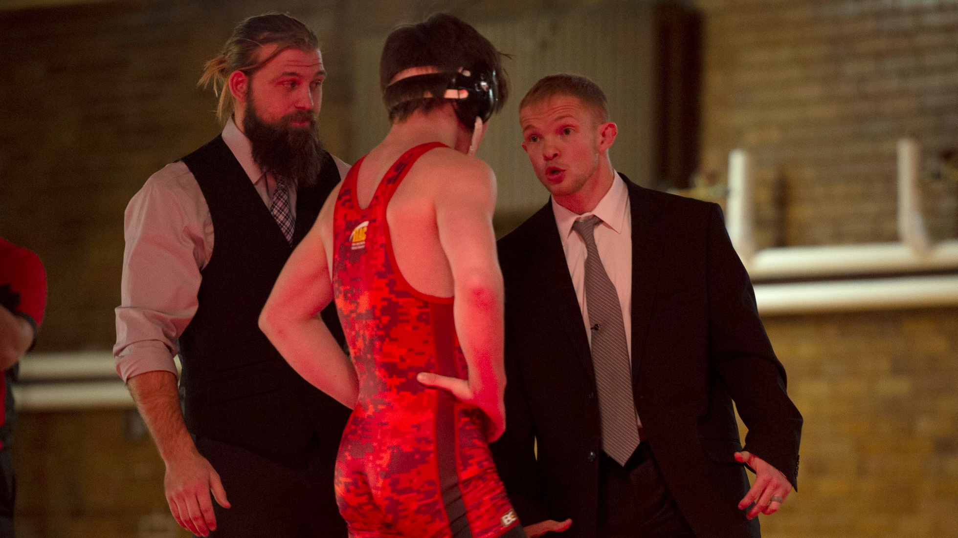 Assistant coach Gunnar Wolfensperger (L) and head coach Dylan Peters talk with Sam McCoy during the dual.