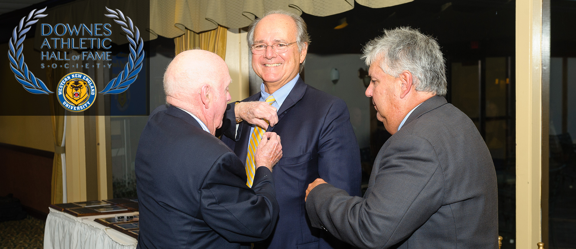 Longtime Western New England coach Bill Downes (left), the inaugural Downes Athletic Hall of Fame inductee, presented University President Dr. Anthony Caprio (middle), a 2005 inductee, with the first Downes Athletic Hall of Fame Society pin at the 2017 induction on September 22 with Athletic Director Joe Sassi (right) looking on. (Photo by Bill Sharon/Spartan SportShots)