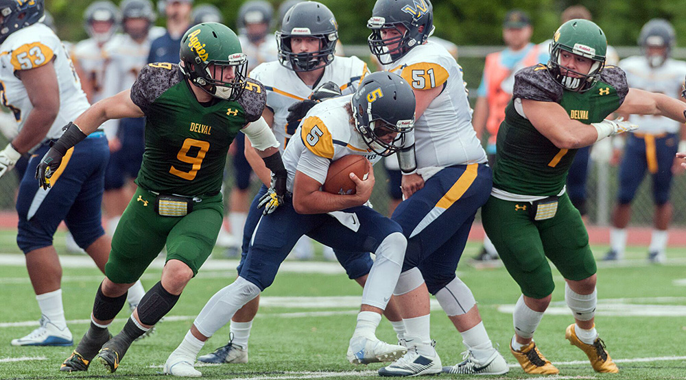 Anthony Nobile, left, and Michael Nobile, converge on the Wilkes quarterback. (Delaware Valley athletics photo)