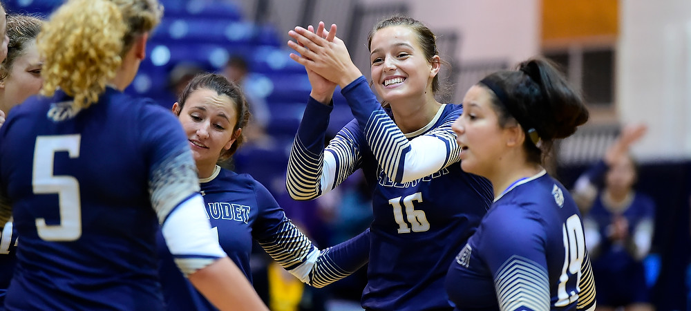 Gallaudet women's volleyball player Karita Lewis claps towards her teammates in a huddle.