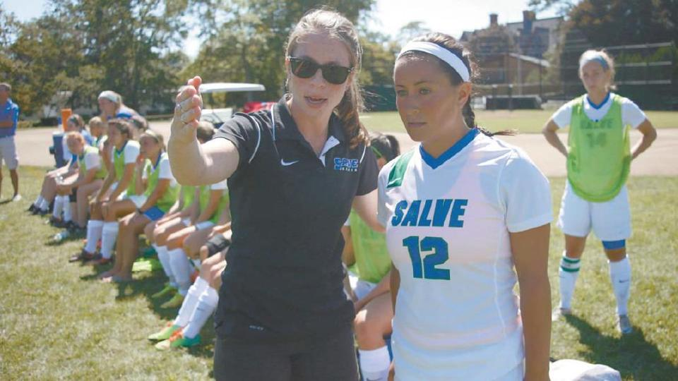 First-year head coach Jane Walsh (left) with senior captain Melissa Figueiredo on sidelines during Saturday's game with Rivier (Photo by Phillip Sherman/Newport Daily News staff photographer).