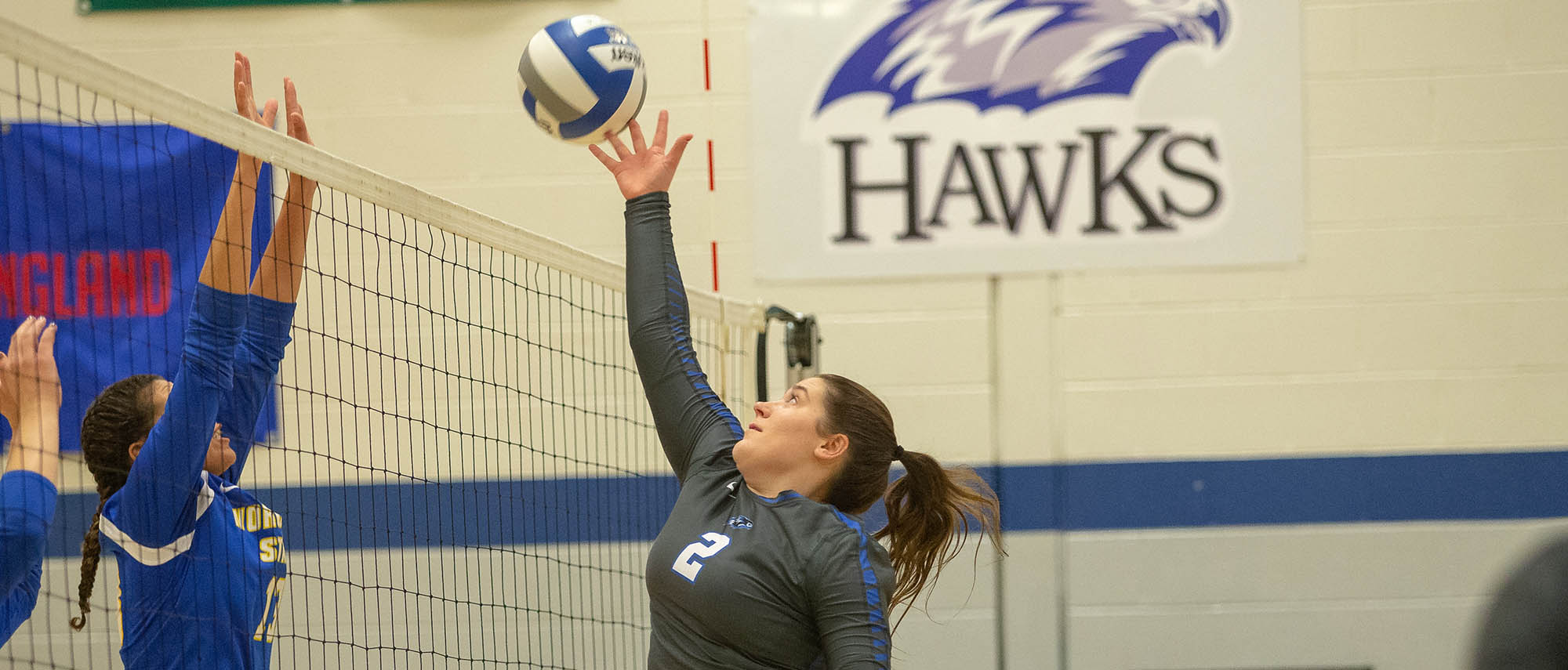 Olivia McGuinnes of the women's volleyball team, attacking against Worcester State