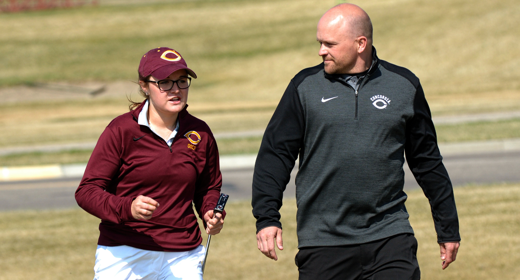 Freshman Katie Krueger talks with head coach Joe Christianson during the first round of the Cobber Open. Krueger placed fifth to earn the first Top 20 finish of her career.