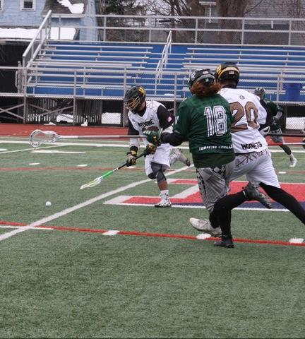 SUNY Broome lacrosse player picking up ball off turf