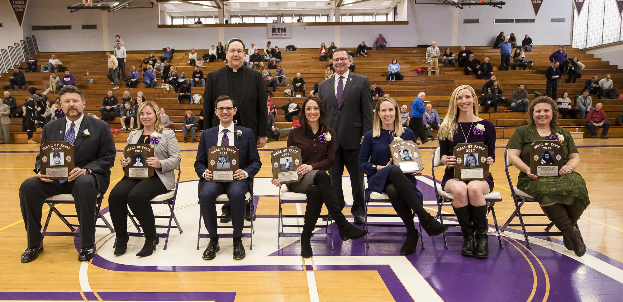 The Wall of Fame Class of 2017, seated from left: Pete Tarutis '92, Patty (Levey) Serpe '88, John Mercuri '07, Jackie (Messantonio) McGovern '07, Allison (Matt) Martin '07, Dr. Taryn Mellody-Liuzzo '07 and Kathy (Loretangeli) Field '93. Standing in back are Rev. Herbert Keller, S.J., interim president of the University, and Dave Martin, director of athletics.