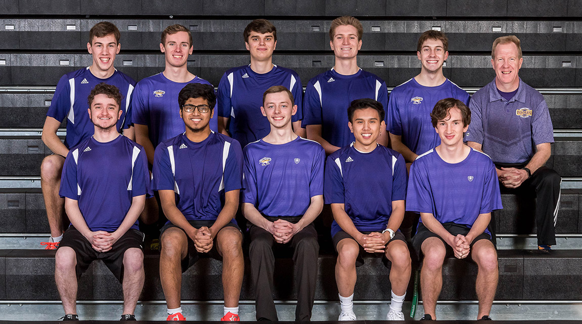 2019-2020 Men's Tennis Team players, in uniform, sitting in two rows on bleachers