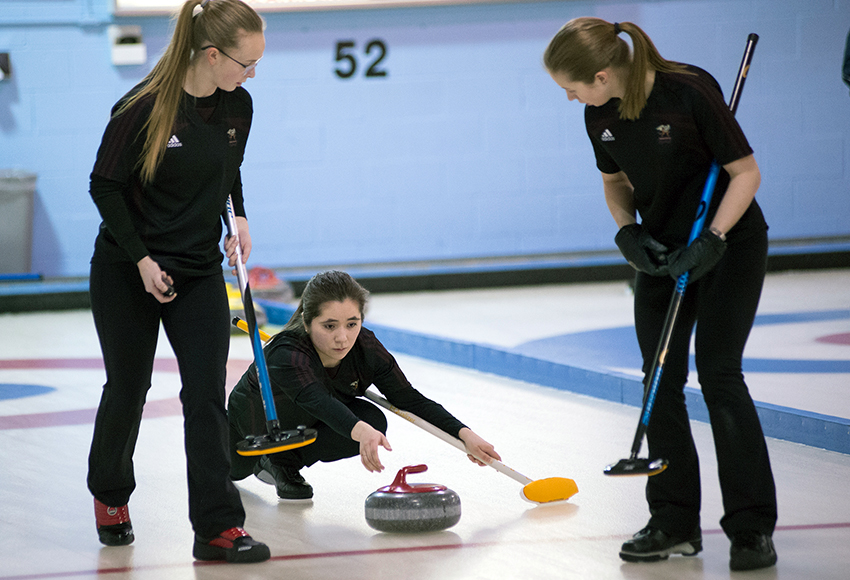 Hilary Charlie throws a rock while teammates Erin Wells, left and Andie Kurjata stand at the ready to sweep during action at the ACAC Winter Regional at Avonair Curling Club on Saturday (Len Joudrey photo).