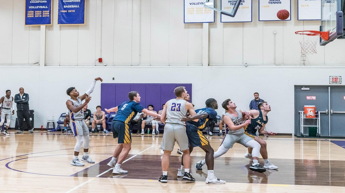 An MCC player just threw a basketball from the free-throw line and ball is in the air approaching the basket. Beneath the basket, two MCC players and three opposing players jockey for position.