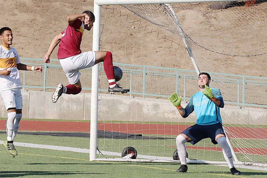 Lancer David Vasquez-Mena goes up high re-direct a free kick by teammate Anthony Jimenez to score the first of his two goals on Tuesday, photo by Richard Quinton.