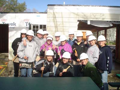 Member of the women's soccer team poses with their hammers and hard hats in front of the home they helped build last Sunday.
