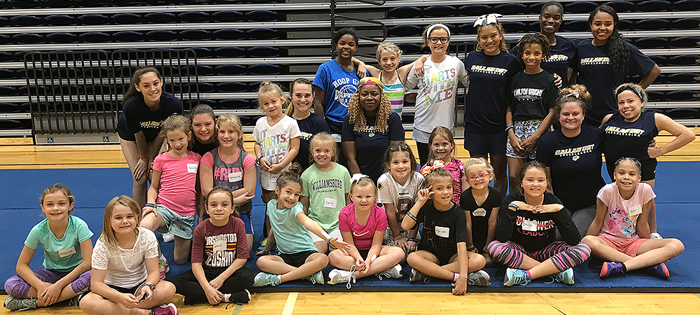 Gallaudet University cheerleaders with youth cheer clinic girls in group photo in Field House.