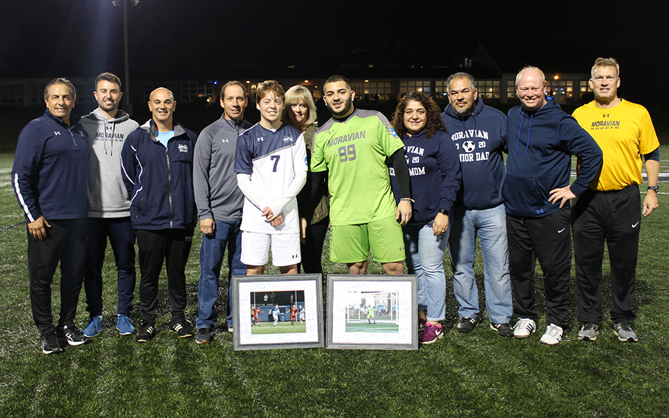 Seniors Jon Matthews and Yamil Yunez with their parents and the Greyhounds' coaching staff on Senior Night prior to defeating DeSales University on John Makuvek Field.