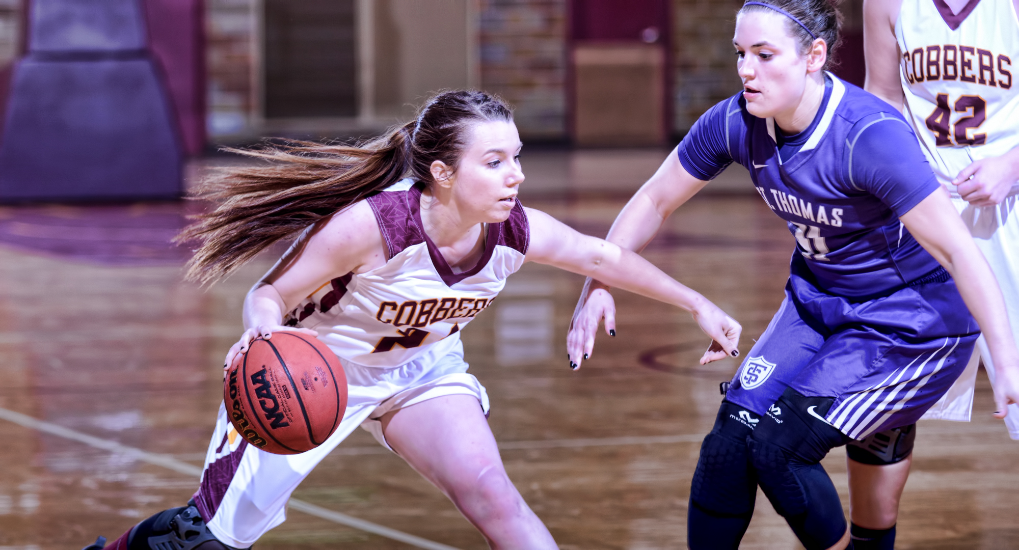 Senior Cassidy Rahman drives around a St. Thomas defender during the Cobbers' game with the nationally ranked Tommies. Rahman finished with five points and two assists. (Photo courtesy of Sam Sabin)