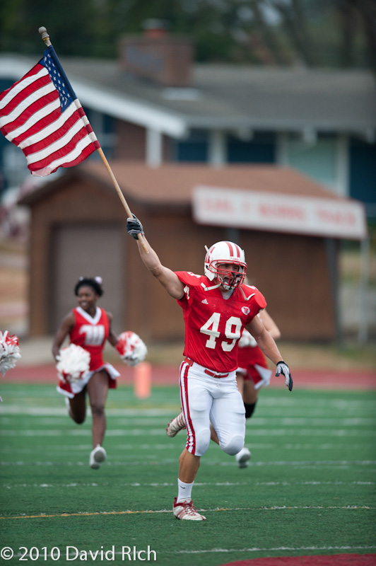 Jonathan Daniels carries the American flag onto Edwards-Maurer Field ahead of his teammates on Sept. 11, 2010, prior to a 52-0 win over Ohio Wesleyan. Photo by David Rich, d3football.com.