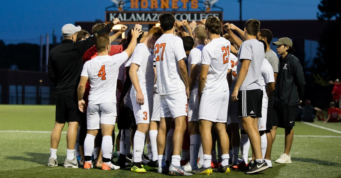 The Kalamazoo College men's soccer team in a huddle.