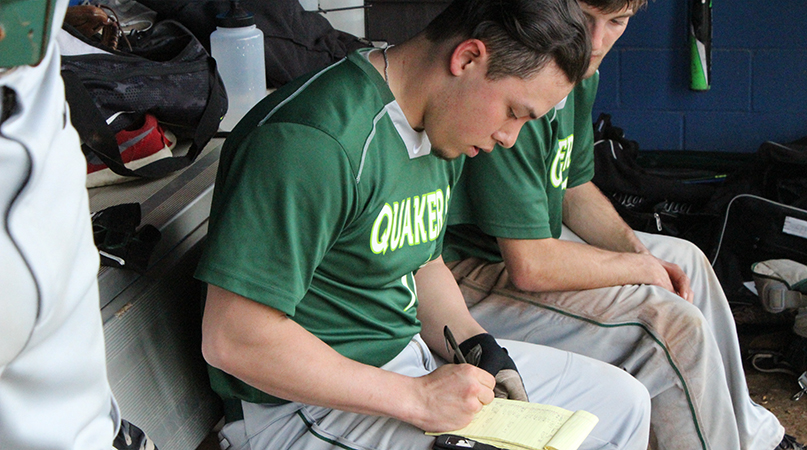 After every at-bat Joshua Chua records relevant data in his notebook. Chua, a transfer, is a vital member on and off the field. (Wilmington Athletic Communications photo)