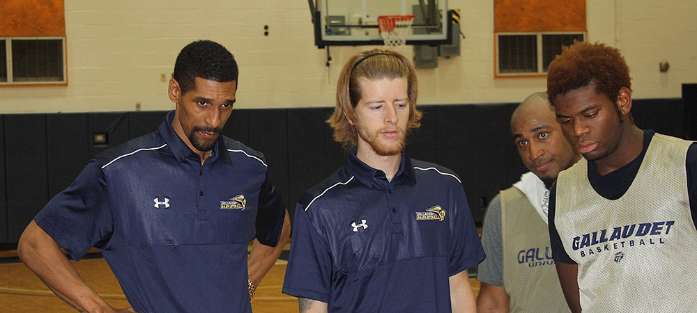 Coach Moten during a timeout with the Gallaudet men's basketball team