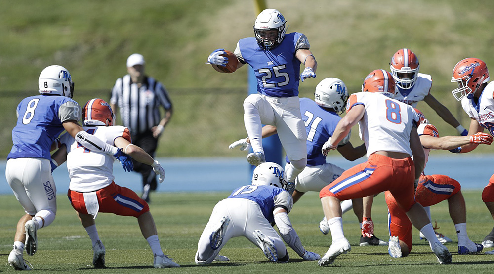 Thomas More's Luke Zajac hurdles over a teammate to try to pick up more yardage against UW-Platteville.