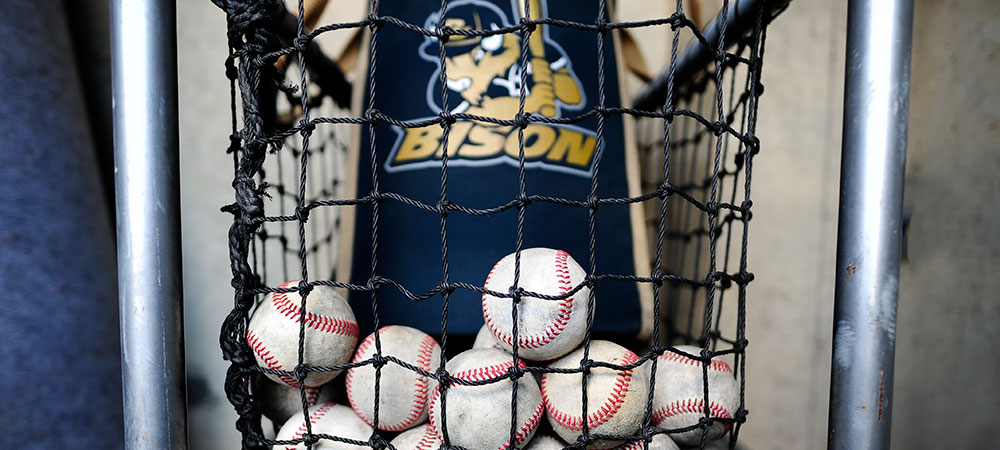 A dozen baseballs sit in a black net in the dugout at the baseball game.