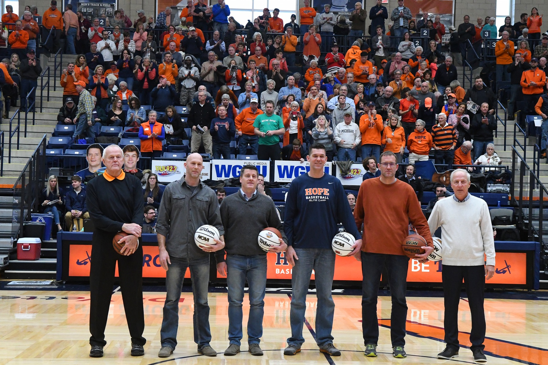 Hope and Calvin men's basketball legends pose together for a picture at halfcourt