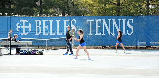 "A tennis player is in the center of the photo wearing a black tank top and blue uniform bottom. A handful of other people are visible in the background as is the text ""Belles Tennis"" on a blue screen hanging on the fence."