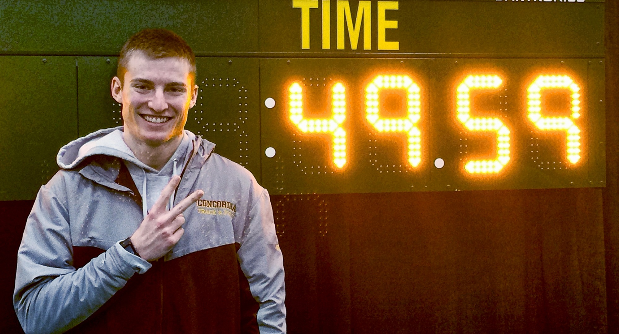 Sophomore David Supinski stands next to his school record time in the 400 meters after breaking his second school record mark over the weekend.