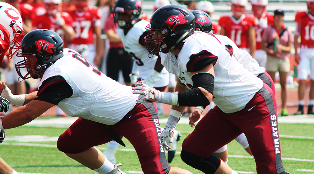 Chad Wilburg and Whitworth defensive line rush the Central quarterback in a Whitworth athletics file photo.