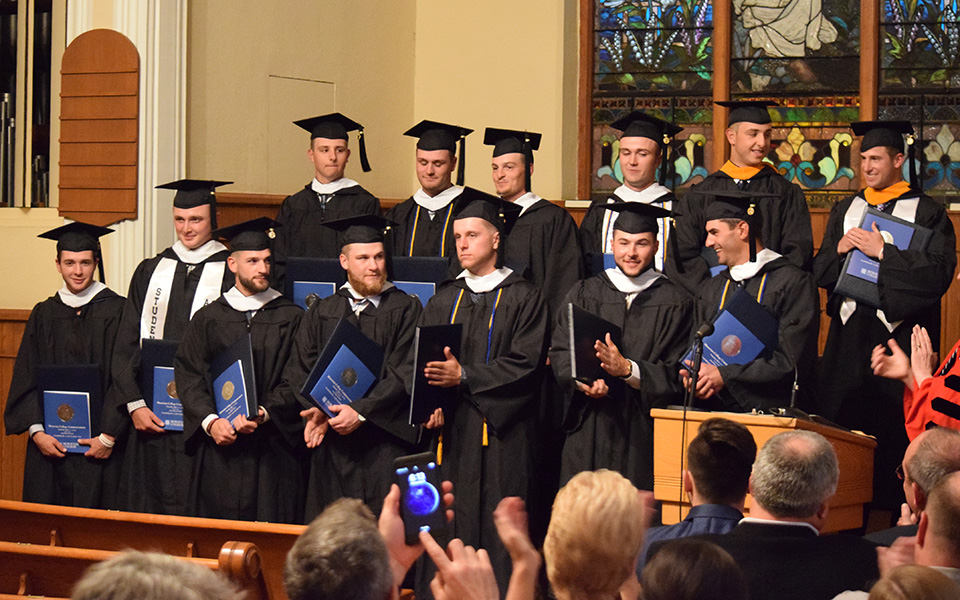 Brendon Caraway, Tyler Caraway, Joey Ferolie, Tim Heard, Rhett Jacoby, Andrew Koenig, Evan Kulig, Steve Lazicki, Austin Markowski, Mike Mittl, Chase Rogers, Billy Roethke and Kevin Shields receive their degrees in a special graduation ceremony on Borhek Chapel.