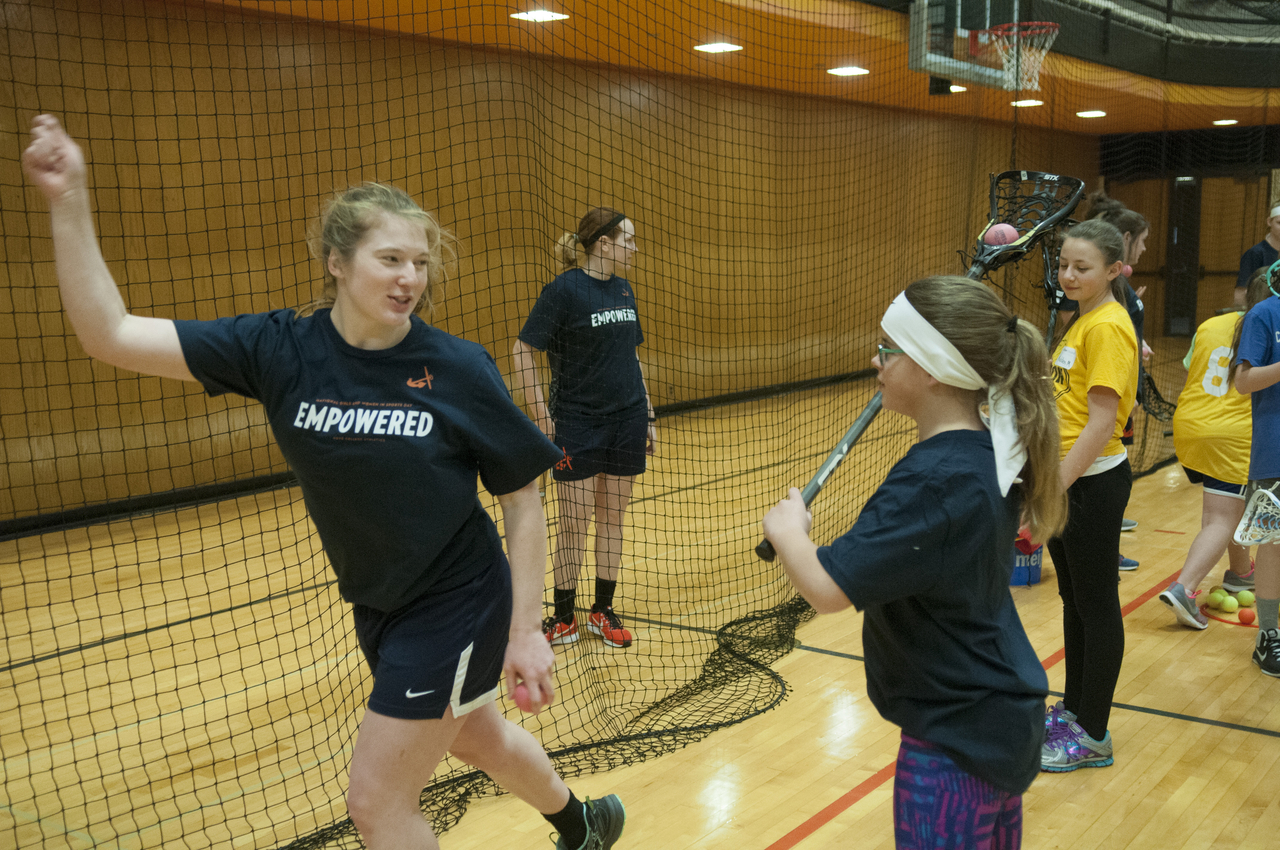 A Hope student-athletes instructs a middle schooler on how to pass with a lacrosse stick.