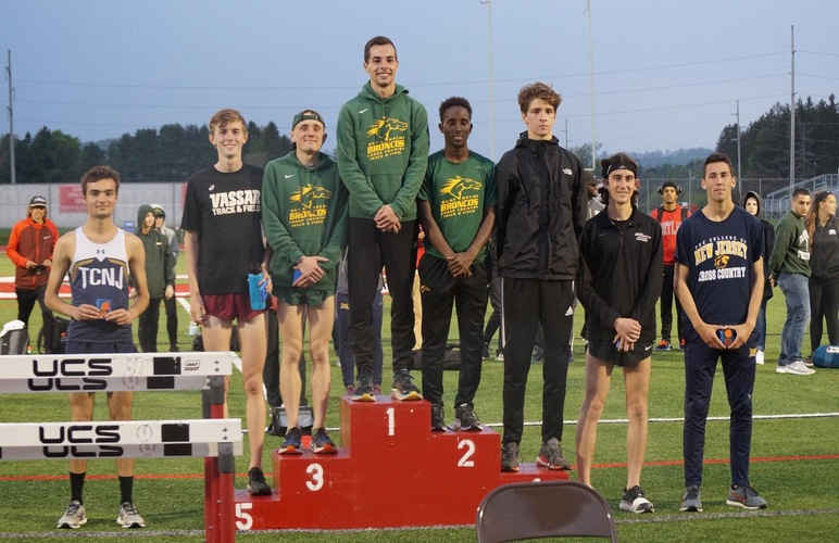 Kobie Lane, Nick Arnecke and Abshir Yerow standing on the top three podium spots following the 5K race at the AARTFC Championships.