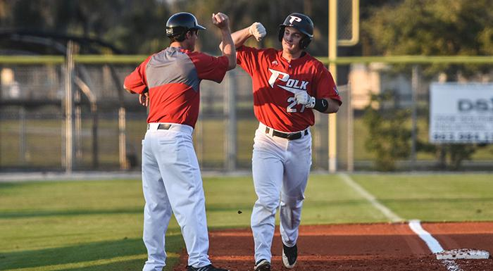 Head Coach Al Corbeil congratulates Zach Diewert after he led off the bottom of the third inning with a solo home run. Diewert also had two doubles, three runs, a walk, and a stolen base. (Photo by Tom Hagerty, Polk State.)
