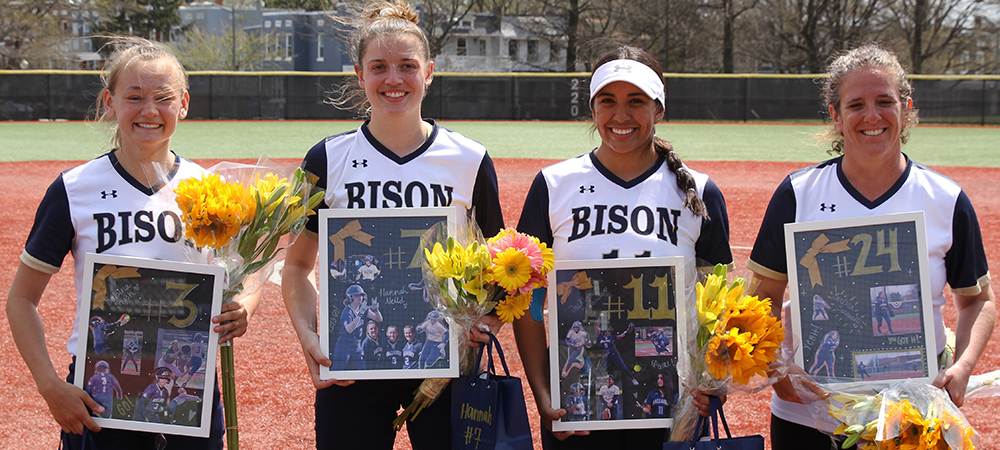 GU's four senior softball student-athletes pose for a group photo on a sunny afternoon. The players hold flowers and a plaque and smile.