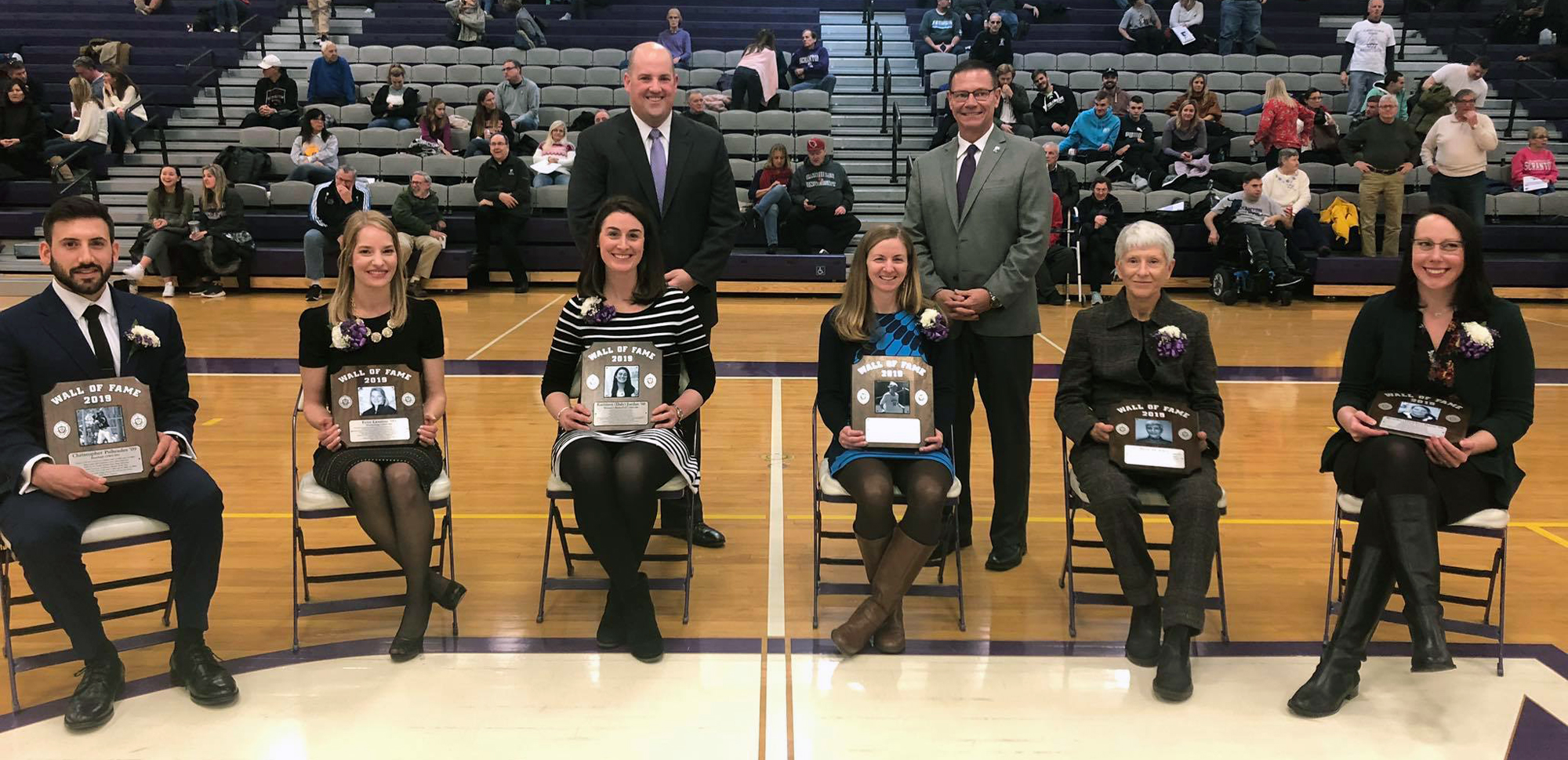 The 2019 Wall of Fame class sitting (L to R): Chris Psihoules '09, Erin (O'Connor) Lentini '09, Kathleen (Daly) Jordan '08, Liz (O'Connor) Huck '04, Beth Howlett and Brooke (Hinkley) Ferro '08. Standing (L to R): Dr. Bobby Davis, Vice President for Student Life & Dave Martin, Direcctor of Athletics.