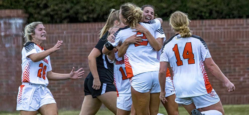 Kenzie Ellenburg is mobbed by her teammates after scoring in the 75th minute of the Pioneers' 1-0 win over Anderson (photo by Chuck Williams)