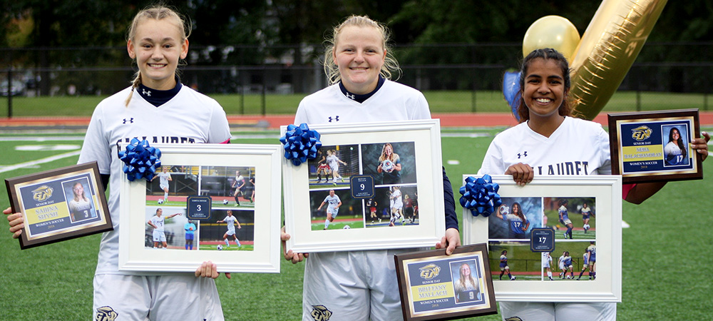 Three Gallaudet women's soccer senior players stand side-by-side with their awards and plaques.
