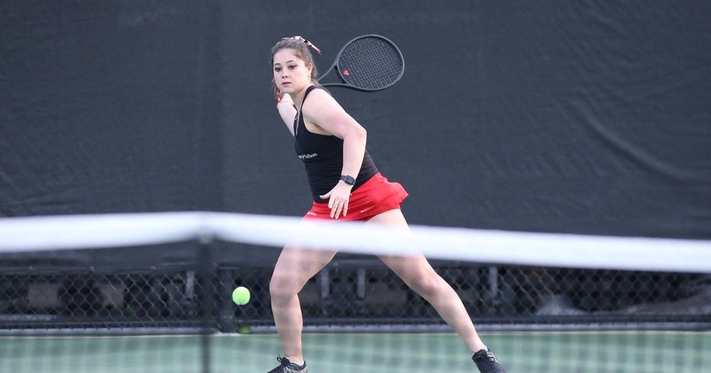 Women's tennis player wearing black tank top and red skirt preparing to return a ball