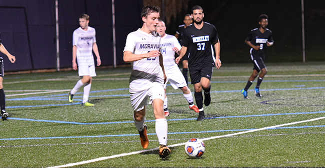 Michael Feeley '21 plays the ball in a match versus Berkeley (N.Y.) College.