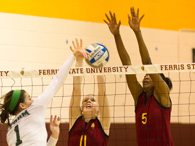 Samantha Fordyce (#11) and Arielle Goodson (#5) block a Lake Erie attack during Saturday's action.  (Photo by Ben Amato)
