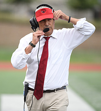 Larry Kindbom, wearing his usual white shirt and red tie, adjust his headset on the sidelines. (Washington University photo by Danny Reise)