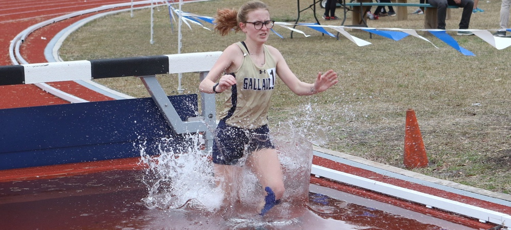 GU's Sierra Pratt jumps into the water pit during the steeplechase as water splashes up on her as she continues to run.