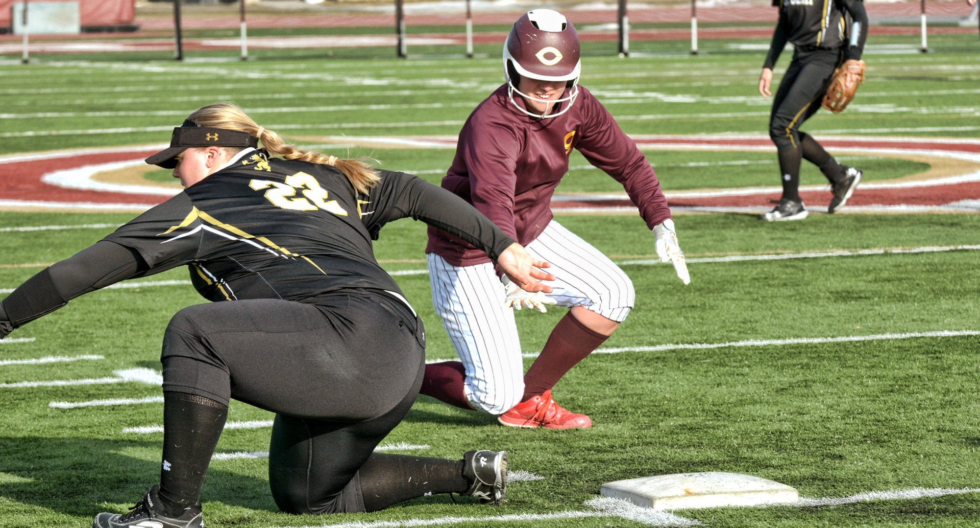 Nicole Johannes dives back into first base on an attempted pickoff play during the second game of the Cobbers' DH with St. Olaf.