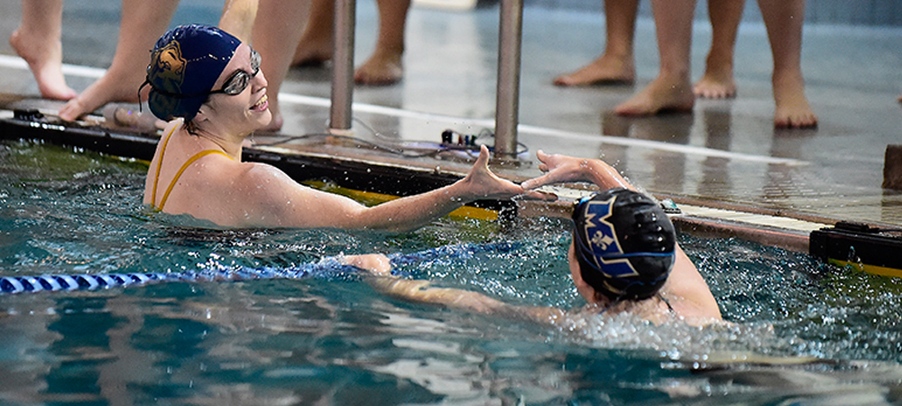 Gallaudet women's swimmer shakes hand with Marymount swimmer while in the pool after an event finished.