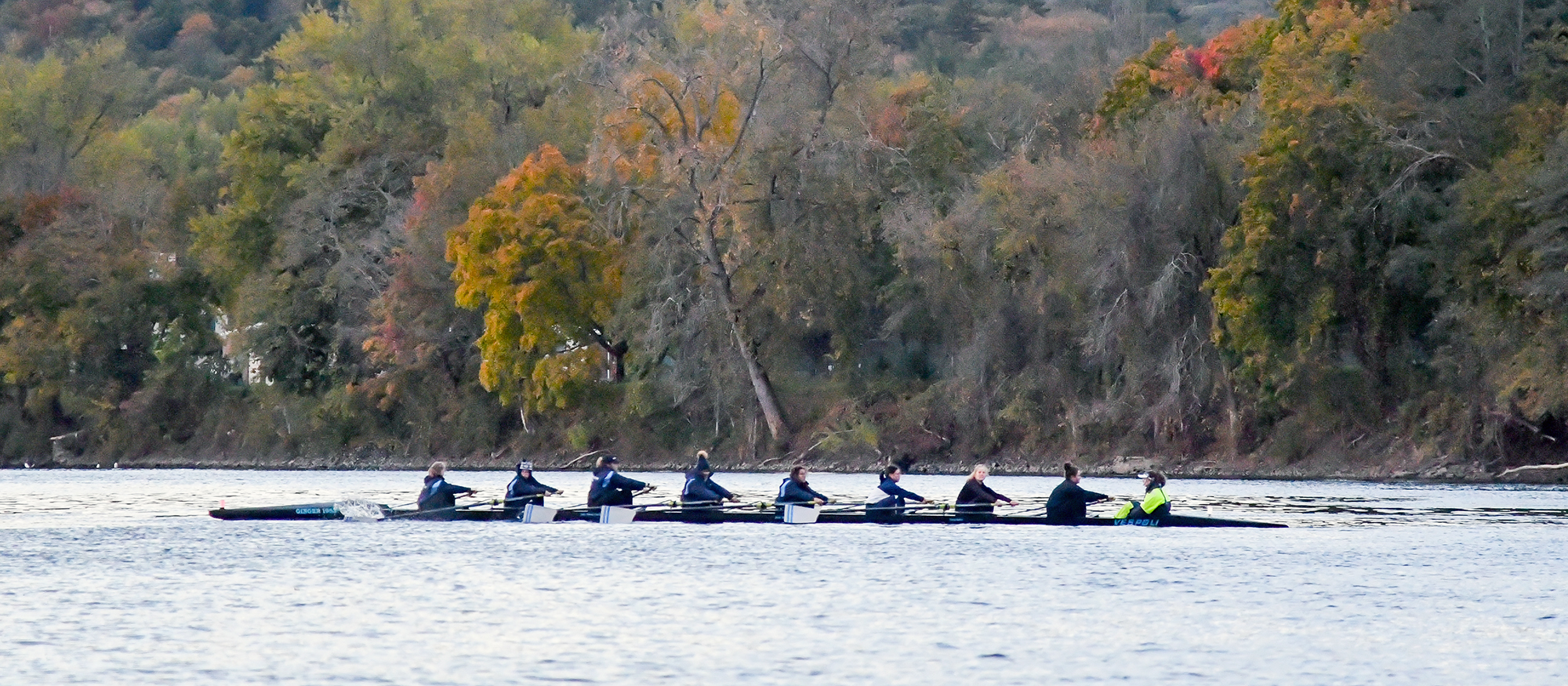 Action photo of the Lyons rowing team on the water of the Connecticut River.