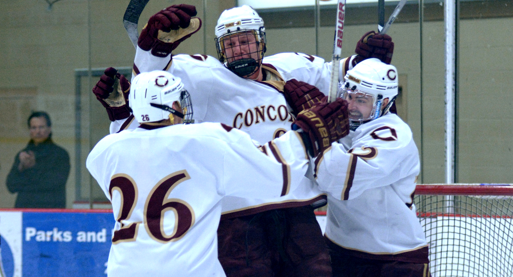Jon Grebosky celebrates his third-period goal against Hamline with teammates Connor Kelly (R) and Quinn Fuchs (#26) during the Cobbers' shootout win over the Pipers.
