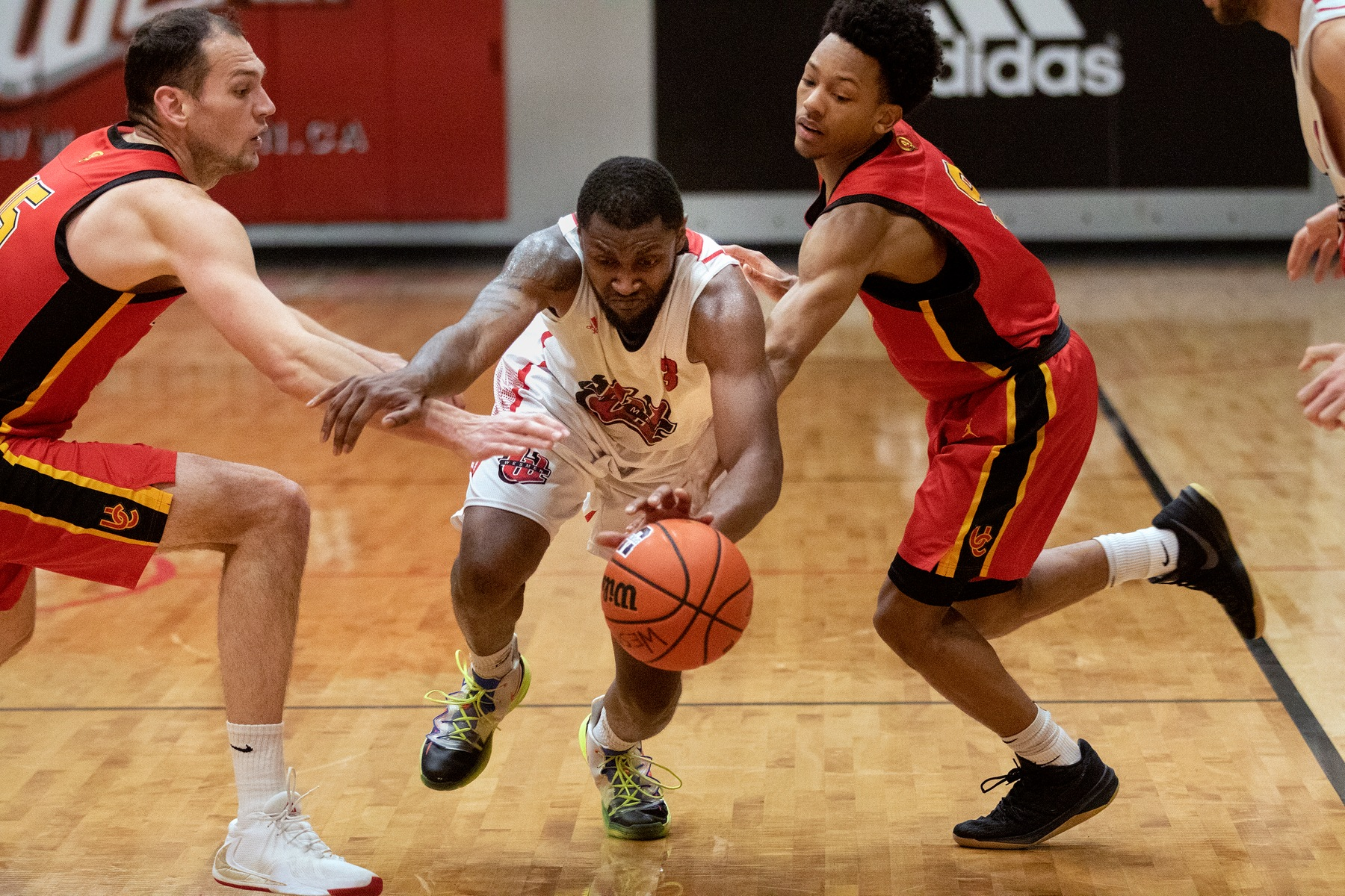 Winnipeg's Narcisse Ambanza (centre) drives between two Calgary Dinos during men's basketball action on Friday, Jan. 17, 2020. (David Larkins/Wesmen Athletics)