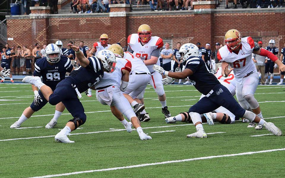 Sophomore Austin Heisler, freshman Tijir Bleam and junior Christian Coia combine on a sack versus King's College on September 1 on the Monarchs' final offensive play of the game to preserve a shutout by the Hounds.