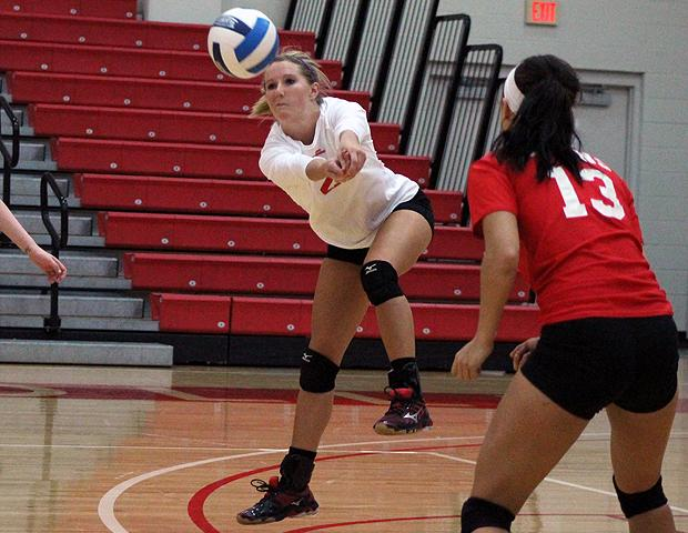 Lisa Urbanski (in white) digs a ball during today's second match against Jackson College. The sophomore totaled 50 digs in today's action. Photo by Nicholas Huenefeld/Owens Sports Information
