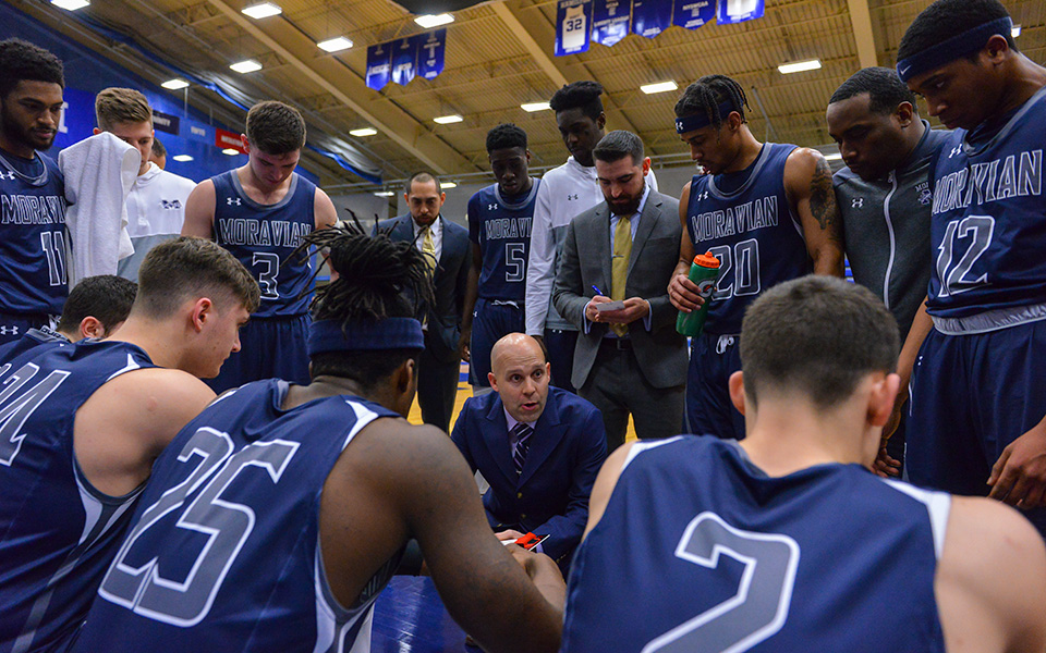 Head Coach Justin Potts talks to the Greyhounds during a timeout in the first half of Moravian's NCAA Division III Tournament First Round win over Keene State (N.H.) College in Clinton, N.Y. - Photo by Josh McKee.