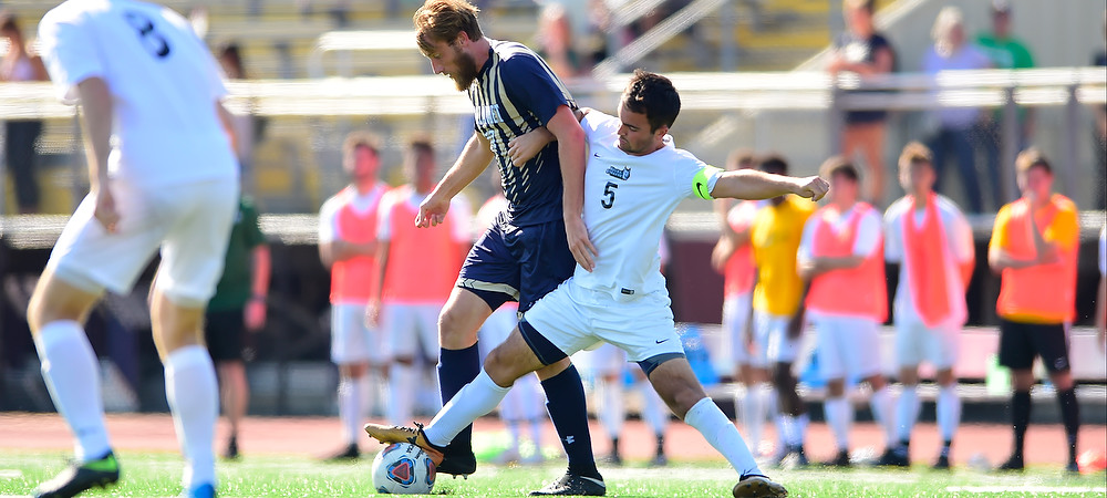 Gallaudet forward Sean Huber gets tripped by a Keuka defender during a day soccer game.