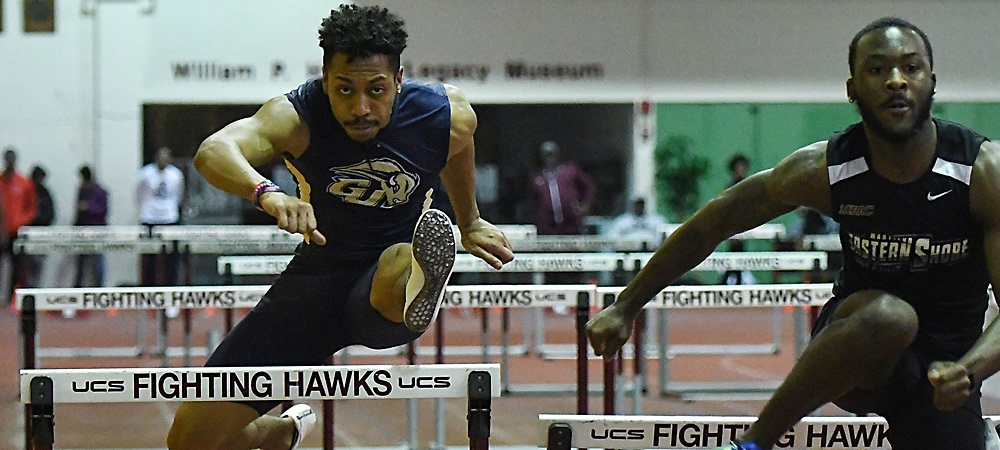 Gallaudet's Michael Haynes hurdles over a hurdle with left leg leading the way.
